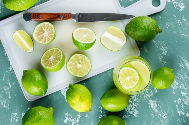 Citroenen met plakjes, mes, limonade plat op gips en snijplank