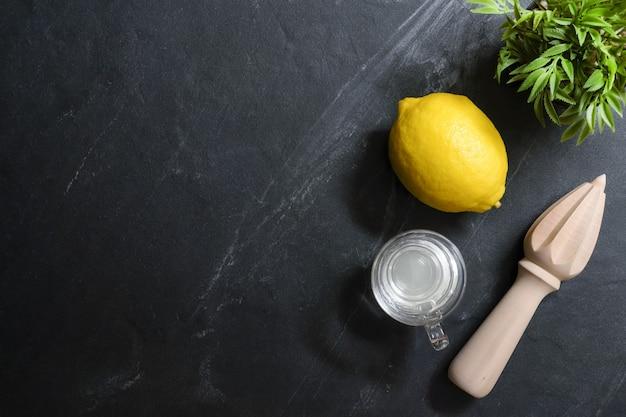 Citroenen met sappers en een glas citroensap staan op de zwarte stenen tafel.