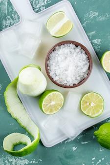 Citroenen met zout, ijsblokjes plat op gips en snijplank