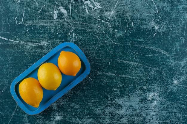Citroenen op een houten bord, op de marmeren tafel.