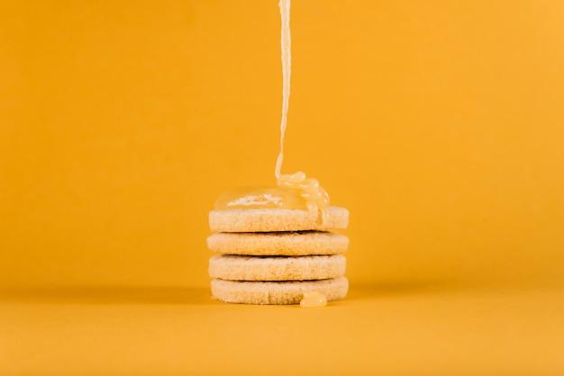 Citroengestremde melk die op gestapelde koekjes op gele oppervlakte druipen