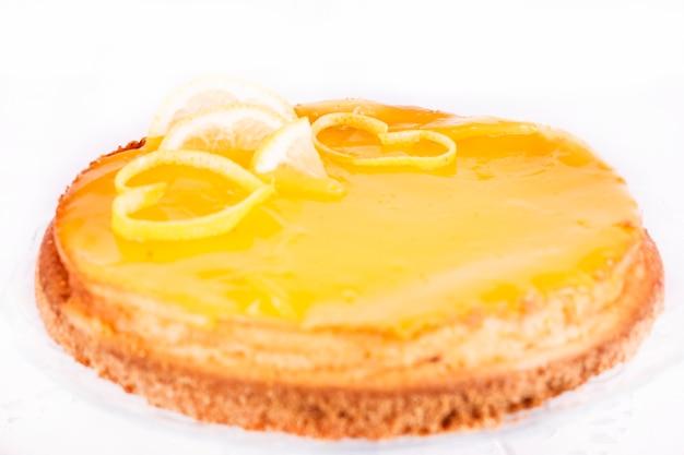 Citroenkaastaart op witte die achtergrond met dichte omhooggaand van de citroenschil wordt verfraaid