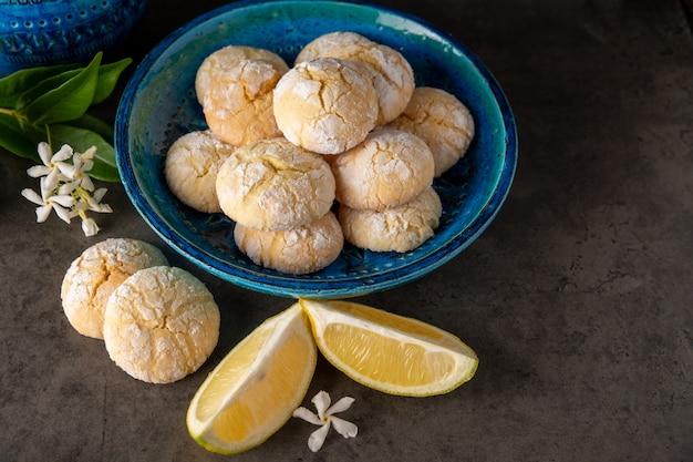 Citroenkoekjes en schijfjes citroen op een donkere tafel met kleine witte bloemen