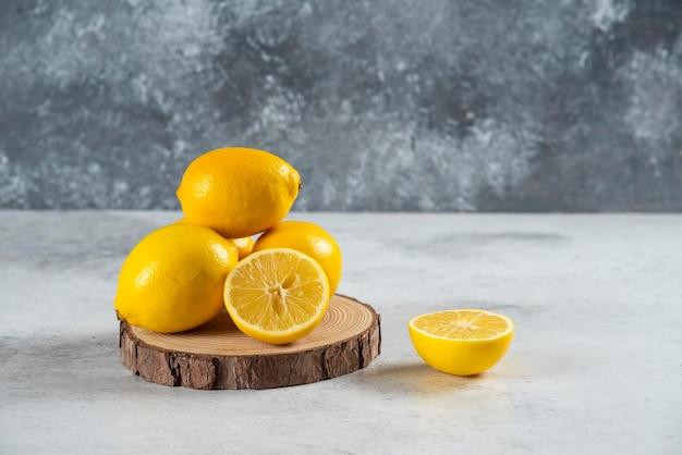 Citroenplakken in houten bord met een hele citroen op marmeren achtergrond.