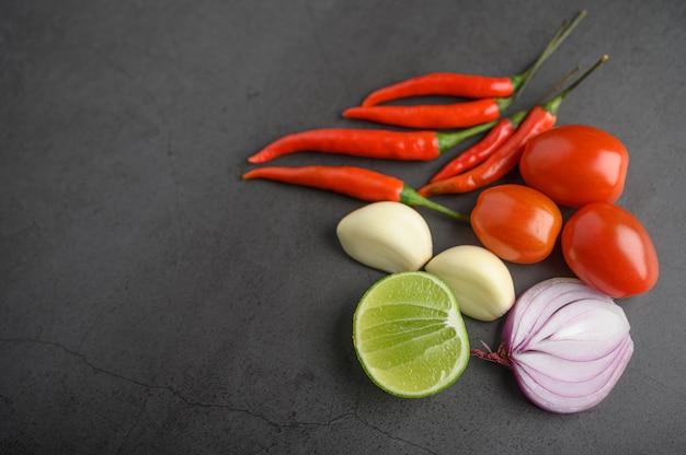 Citroenplakken, sjalotten, knoflook, tomaten en paprika's op een zwarte cementvloer.