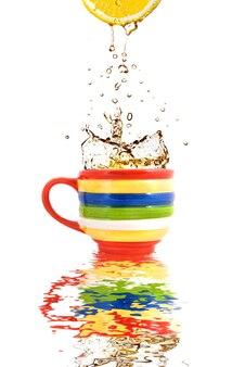 Citroensap en scheutje thee in kleur beker met reflectie