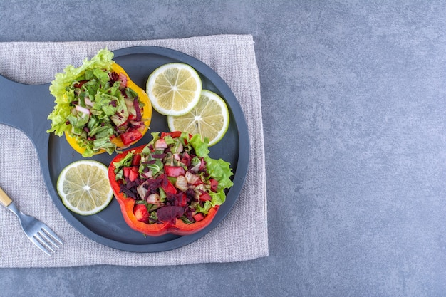 Citroenschijfjes met twee porties salades in peperschijfjes op een serveerschaal op marmeren ondergrond