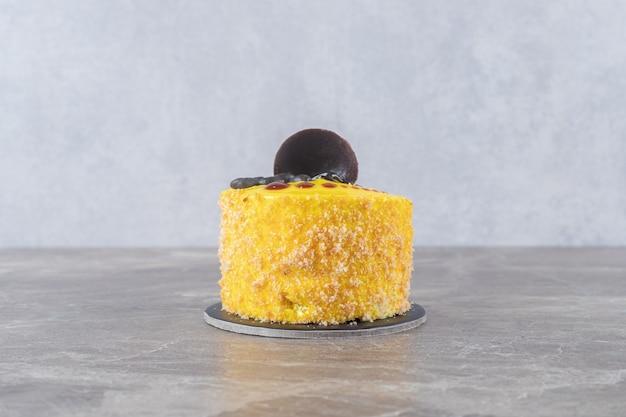 Citroensmaakcoating op een kleine cake op een marmeren oppervlak