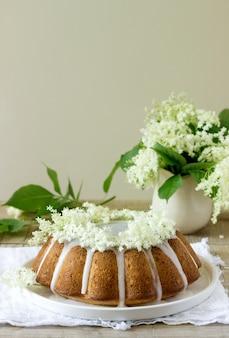 Citroentaart met een glazuur van suiker en vlierbloesemsiroop, versierd met vlierbessenbloemen. rustieke stijl.