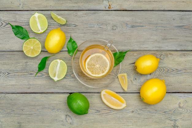 Citroenthee met citroen en limoen op houten tafel