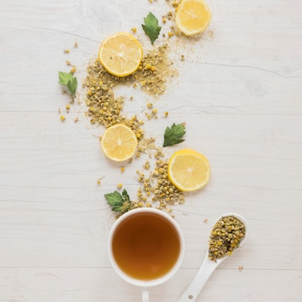 Citroenthee met gedroogde chinese chrysant bloemen en citroen plakjes op houten tafel