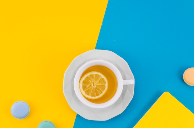 Citroentheekop met makarons op gele en blauwe dubbele achtergrond