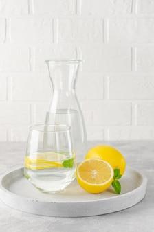 Citroenwater met verse citroenen en muntblaadjes op een grijze betonnen achtergrond. een gezond drankje. kopieer ruimte.