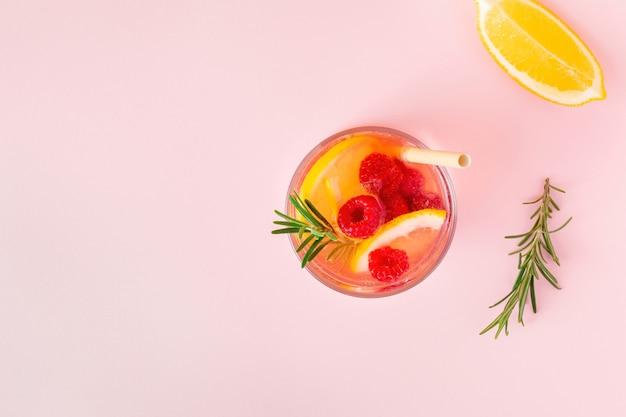 Citroenwater of limonade met framboos en rozemarijn op een roze achtergrond, bovenaanzicht. aromatische koele cocktail voor de zomerse hitte.