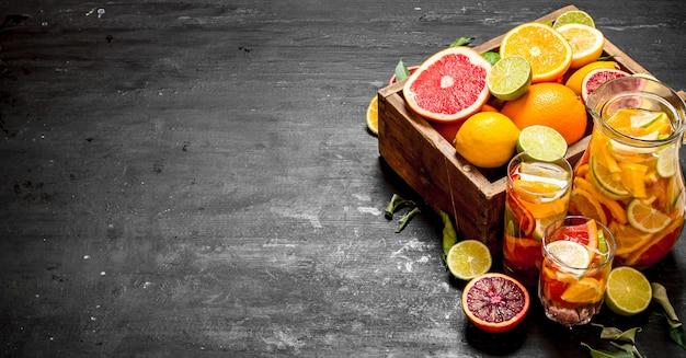 Citrus achtergrond. vers citroensap met plakjes limoenen, sinaasappels, grapefruits en citroenen. op zwart bord.