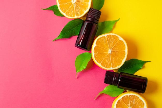 Citrus etherische olie. gesneden citrusvruchten en aromaflessen op roze achtergrond