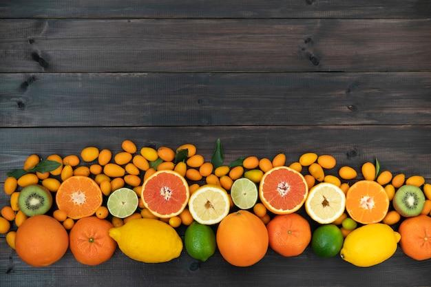 Citrus gemengde sinaasappelen, mandarijnen, kiwi, citroenen en limoen liggen op een zwarte houten achtergrond van planken.