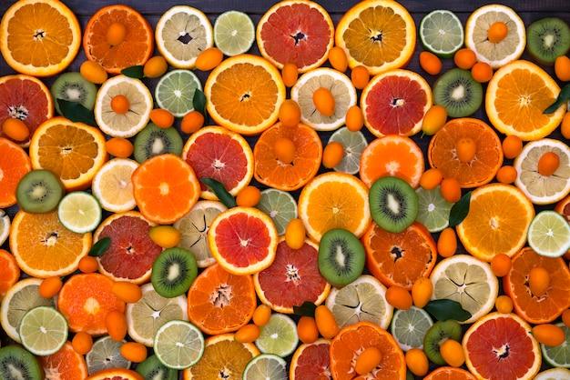 Citrus gemengde sinaasappelen, mandarijnen, kiwi, citroenen en limoen liggen op een zwarte houten