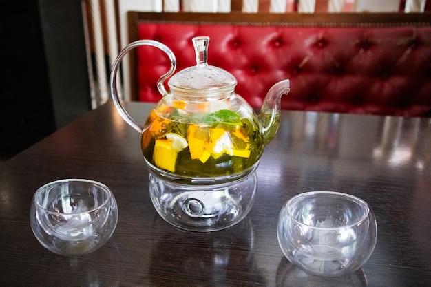 Citrus groene thee in transparante glazen theepot en twee glazen kopjes op een houten tafel.