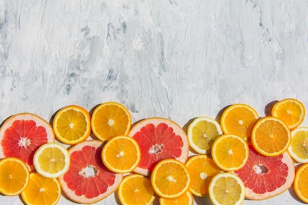 Citrus vruchten. sinaasappel, citroen, grapefruit, op een trendy stenen achtergrond bovenaanzicht, plat gelegd