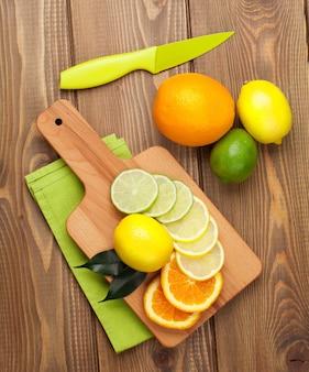 Citrus vruchten. sinaasappels, limoenen en citroenen. over houten tafel achtergrond