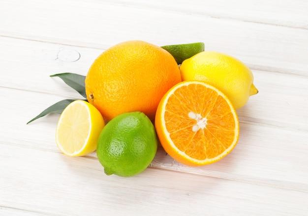 Citrus vruchten. sinaasappels, limoenen en citroenen. over witte houten tafel achtergrond