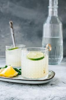 Citruscocktail met citroensap en limoen in een glas op tafel