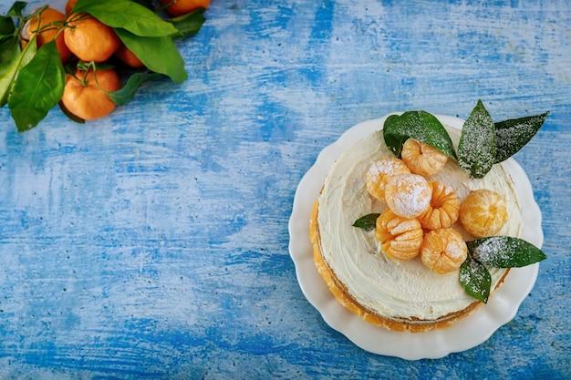 Citruspastei met verse mandarijn en bladeren. bovenaanzicht.
