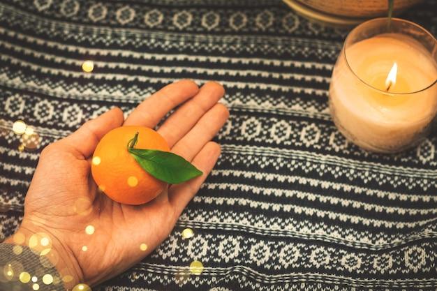 Citrusvoedsel bij wintersamenstelling op backhround van gebreide trui bij gezellig huis, kopieer ruimte met kaars. hoge kwaliteit foto