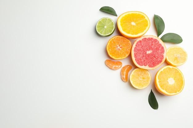 Citrusvruchten en bladeren op witte achtergrond, ruimte voor tekst