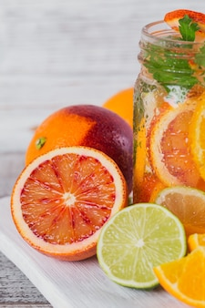 Citrusvruchten en kruidenwater voor detox of dieet in glazen flessen op een houten bord