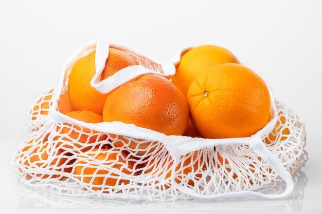 Citrusvruchten in witte koordzak die op witte achtergrond wordt geïsoleerd. sinaasappel, grapefruit, mandarijn. geen plastic.