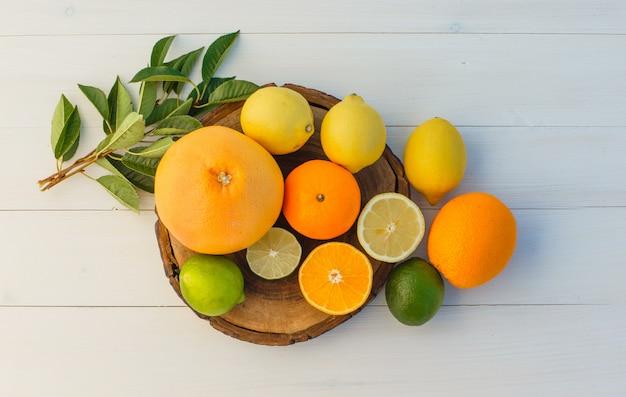 Citrusvruchten met bladeren op snijplank en houten achtergrond, bovenaanzicht.