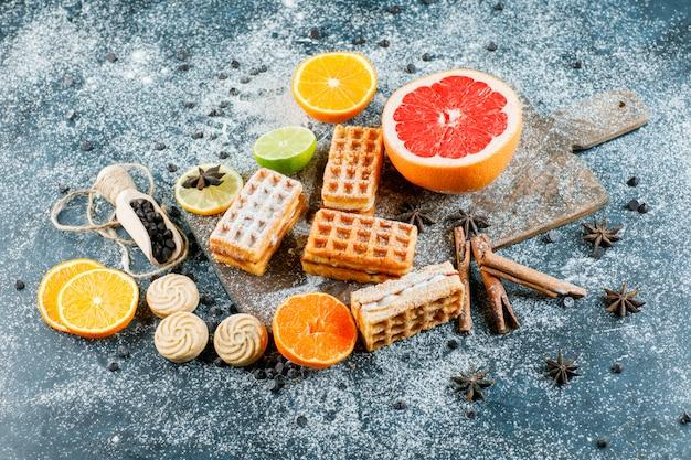 Citrusvruchten met wafel, kruiden, koekjes, chocoladeschilfers plat lag op grungy en snijplank tafel
