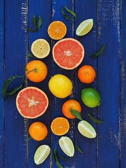 Citrusvruchten op blauwe houten oppervlak - sinaasappels, citroenen, limoen, mandarijnen en grapefruit