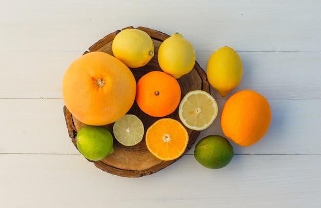 Citrusvruchten op snijplank en houten achtergrond. plat leggen.