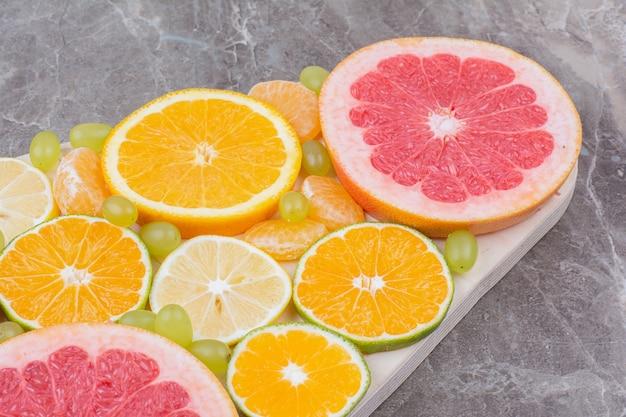 Citrusvruchten plakjes en druiven op een houten bord.