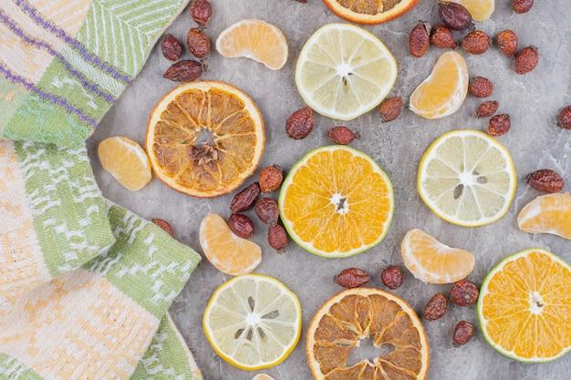 Citrusvruchten plakjes en rozebottels op stenen achtergrond.