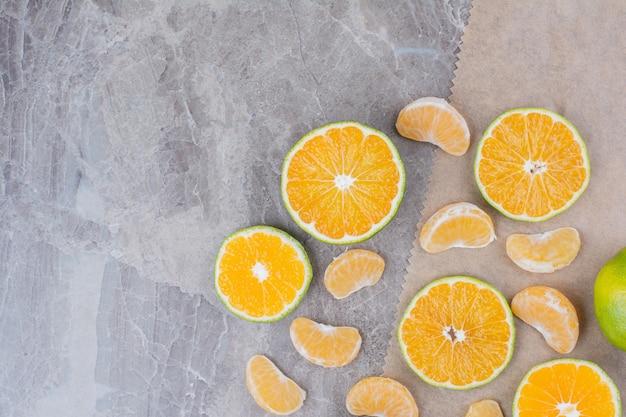 Citrusvruchten plakjes verspreid over stenen achtergrond.