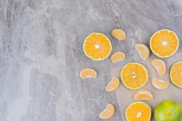 Citrusvruchten verspreid over stenen achtergrond.