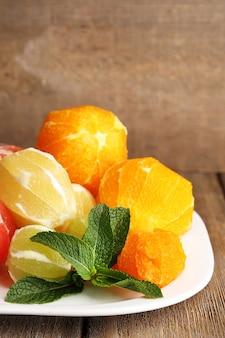 Citrusvruchten zonder schil, op plaat, op houten ondergrond