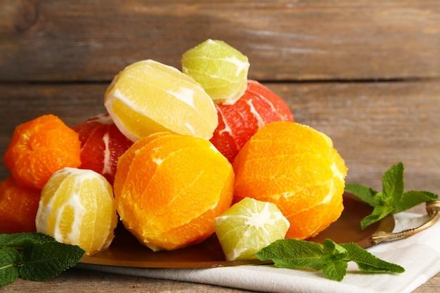 Citrusvruchten zonder vel op dienblad, op houten tafel