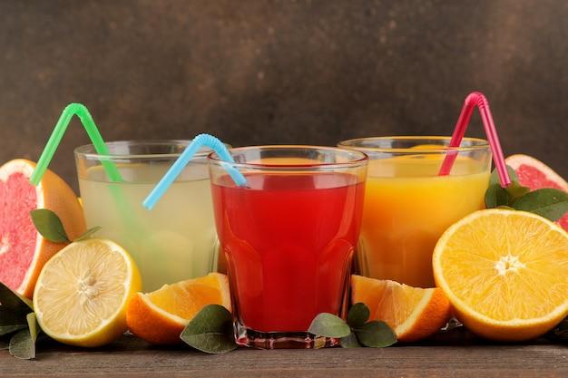 Citrusvruchtensappen. citroen, grapefruit en sinaasappelsap met vers fruit op een bruine houten tafel