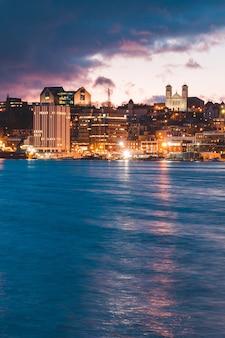 Cityscape dichtbij waterlichaam onder blauwe hemel tijdens nacht