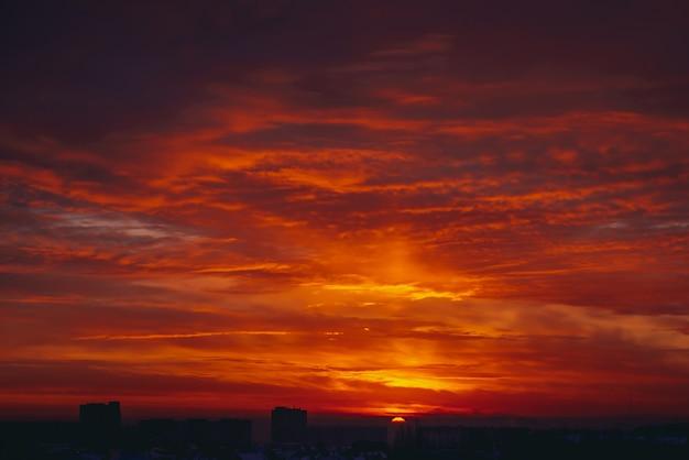 Cityscape met levendige vurige dageraad. verbazingwekkende warme dramatische bewolkte hemel boven donkere silhouetten van stadsgebouwen. oranje zonlicht. atmosferische achtergrond van zonsopgang bij bewolkt weer. copyspace.