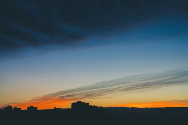 Cityscape met prachtige varicolored levendige dageraad. verbazingwekkende dramatische blauwe wolk hemel boven donkere silhouetten van stad bouwen daken.