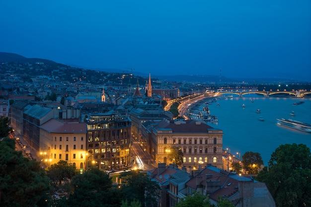 Cityscape uitzicht op de donau in de nacht met grote lichtgevende brug in boedapest.
