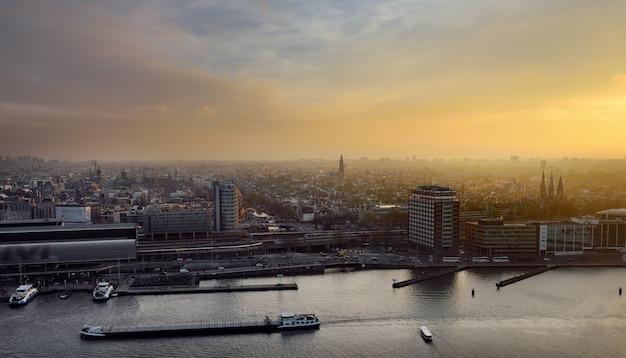 Cityscape van amsterdam hoogste mening bij zonsondergang. rivier met schepen, boten, centraal station. sightseeing van het nederlands.