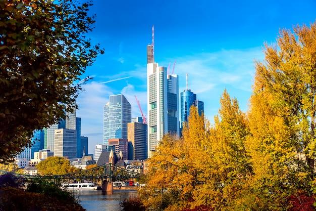 Cityscape van de horizon van frankfurt, duitsland met brug en wolkenkrabbers tijdens zonnige dag in de herfst.