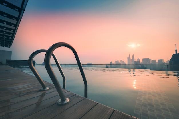 Cityscape van kuala lumpur stadshorizon met zwembad op het dak van hotel bij zonsopgang in maleisië.